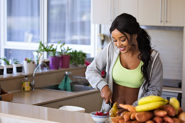 African American woman cutting fruit - healthy weight loss fitness